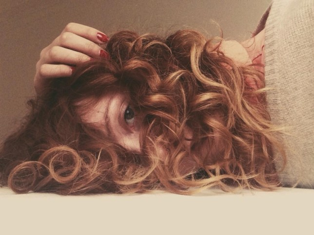 A portrait of a young woman with long curly hair lying down and looking at camera Ailine Liefeld / EyeEm/Ailine Liefeld / EyeEm