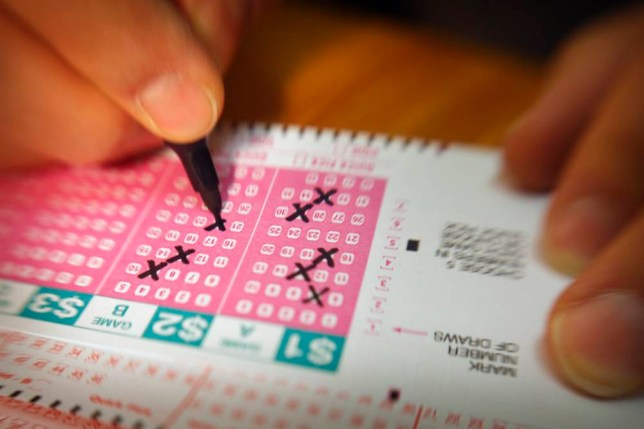 Person filling out lottery ticket, close-up