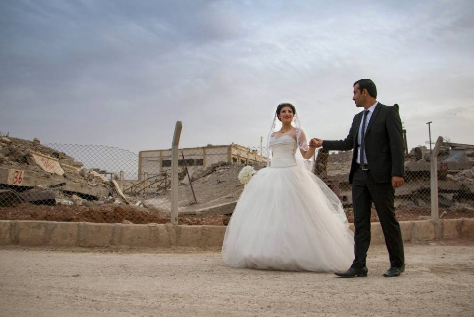 A groom holds his bride's hand while walking past damaged buildings as they head to their wedding ceremony in the northern Syrian town of Kobani, October 23, 2015. This Kurdish couple is the first to have a civil marriage after the town was captured from Islamic State by Kurdish-led forces and it was declared part of the system of autonomous self government established by the Kurds. Picture taken October 23, 2015. REUTERS/Rodi Said EDITORIAL USE ONLY. NO RESALES. NO ARCHIVE