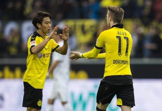 Dortmund's forward Marco Reus (R) celebrates scoring his side's 3rd goal with Dortmund's Japanese midfielder Shinji Kagawa during the German first division football Bundesliga match between Borussia Dortmund and FC Augsburg on October 25, 2015 in Dortmund, western Germany. AFP PHOTO / ODD ANDERSEN RESTRICTIONS: DURING MATCH TIME: DFL RULES TO LIMIT THE ONLINE USAGE TO 15 PICTURES PER MATCH AND FORBID IMAGE SEQUENCES TO SIMULATE VIDEO. ==RESTRICTED TO EDITORIAL USE == FOR FURTHER QUERIES PLEASE CONTACT THE DFL DIRECTLY AT + 49 69 650050.ODD ANDERSEN/AFP/Getty Images