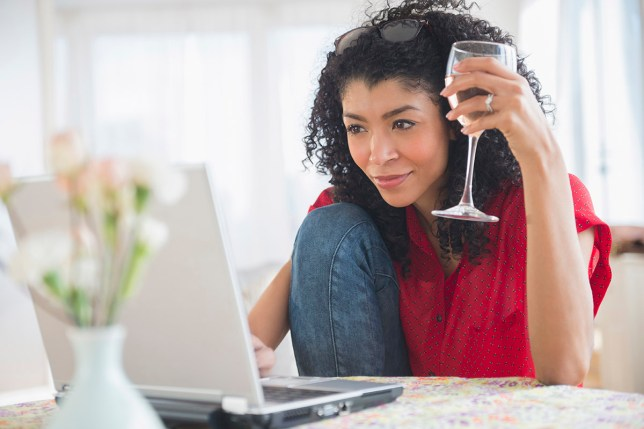 Mixed race woman drinking wine and using laptop