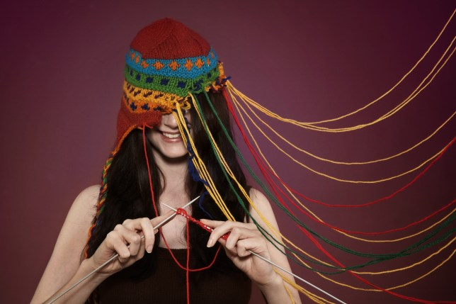 Lady knitting on her own hat (Picture: Getty)