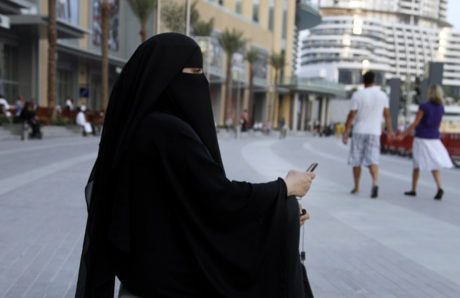 Mandatory Credit: Photo by Jochen Tack/imageBROKER/REX Shutterstock (4566102a) Arab woman in traditional black dress, the abaya, with cell phone, Dubai Mall, Dubai, United Arab Emirates, Middle East VARIOUS