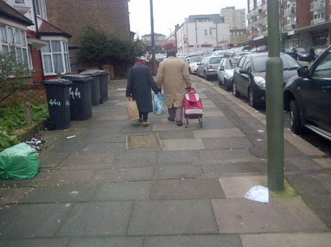Elderly couple, in Facebook pic, share the weight of a shopping bag by holding hands