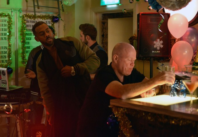 WARNING: Embargoed for publication until 00:00:01 on 01/12/2015 - Programme Name: EastEnders - TX: 10/12/2015 - Episode: 5187 (No. n/a) - Picture Shows: Vincent places something in Phil's jacket pocket. Vincent (RICHARD BLACKWOOD), Phil Mitchell (STEVE MCFADDEN) - (C) BBC - Photographer: Kieron McCarron