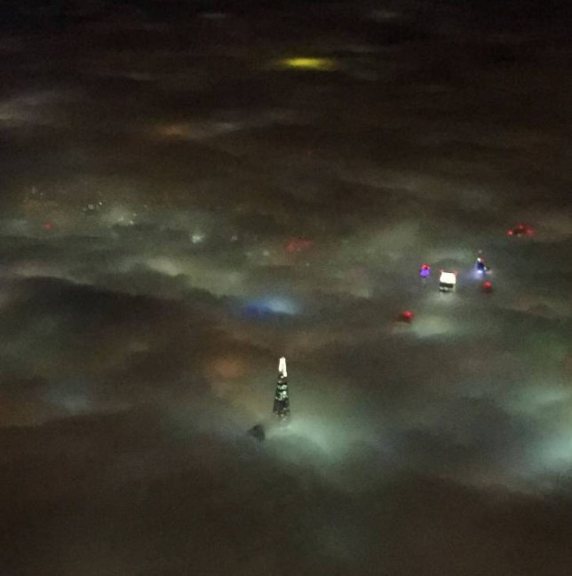 """BEST QUALITY AVAILABLE Handout photo taken with permission from the Twitter feed of @sarahjwells of a foggy London skyline from the air on the approach to City Airport, London, as air passengers face a second day of disruption as another raft of flights are cancelled due to dense fog. PRESS ASSOCIATION Photo. Picture date: Sunday November 1, 2015. Around 45 flights, 10% of departures from Heathrow airport, have been """"pre-cancelled"""" as a yellow weather warning for fog covers much of England and east Wales. See PA story AIR Fog. Photo credit should read: @sarahjwells/PA Wire NOTE TO EDITORS: This handout photo may only be used in for editorial reporting purposes for the contemporaneous illustration of events, things or the people in the image or facts mentioned in the caption. Reuse of the picture may require further permission from the copyright holder."""