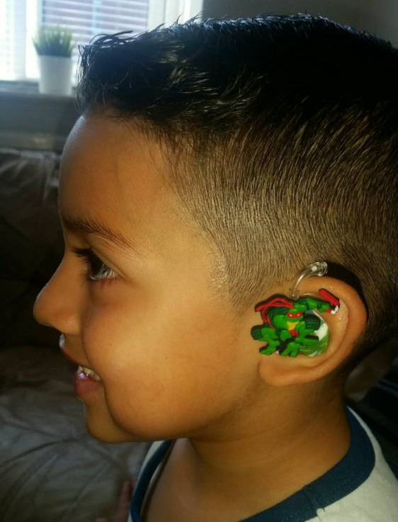"""Collect photos of the Teenage Mutant Ninja Turtle cartoon hearing aid cover. See SWNS story SWHEAR; A mum has helped her deaf son beat the bullies by putting colourful cartoon covers - on his HEARING AIDS. Little Santiago Lozada was diagnosed with deafness earlier this year after having trouble concentrating at school and ordered to wear two hearing aids. Nathalie Lozada, 32, was horrified when she realised her five-year-old son was being teased at school because of his new hearing aids, which he hated wearing, so she decided to stick his favourite cartoon characters on the sides. Nathalie, a deputy nursery nurse, said: """"He was given hearing aids but associates them with his school uniform so doesn't like to wear them."""""""