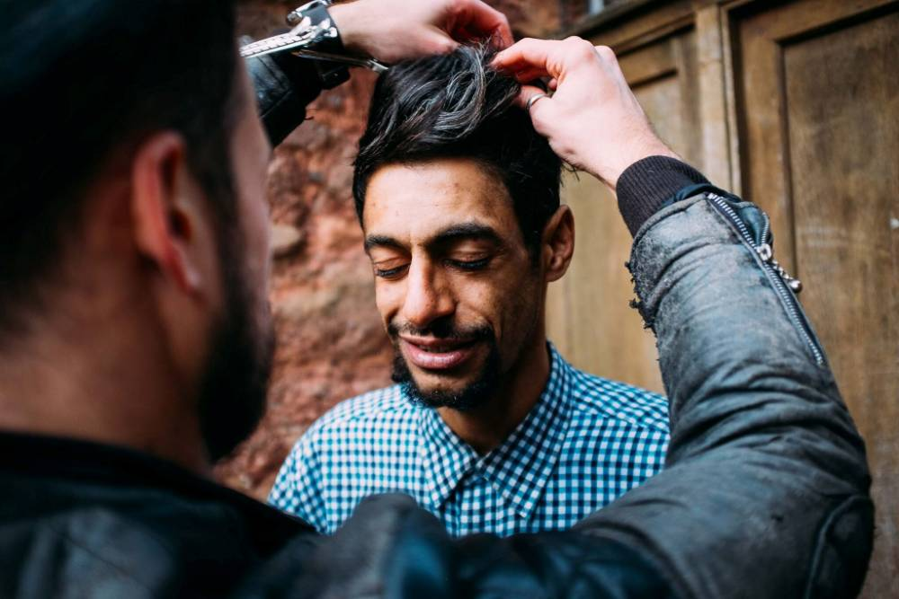 Joshua Coombes, 28, giving out free hair cuts to homeless people in Exeter. See SWNS story SWCUT; A barber is helping the homeless - by venturing into the streets and giving them free HAIRCUTS. Hairdresser Joshua Coombes, 28, is hoping his actions will help make a difference and influence people to help rough sleepers. He was inspired after a trip to New York, where he saw a professional hairdresser cutting homeless people's hair, and decided to give it a go when he returned to Exeter, Devon. Despite working full time in Jeff Goodwin's salon in Exeter, Josh often finds himself dealing with queues after work, when he helps the homeless.