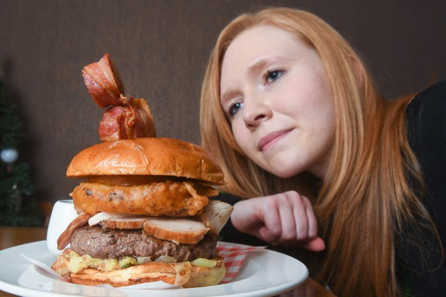 PIC BY IAIN WATTS/MERCURY PRESS (PICTURED: RESTAURANT CUSTOMER KATE COLLINS EYES UP THE CHRISTMAS DINNER BURGER) This mammoth festive meal crams an ENTIRE Christmas dinner into a burger. Eddie and Kate Weightsí monster creation features a juicy 9oz rump steak burger, massive beer-battered onion ring, gravy-filled Yorkshire pudding and 7oz of smoked turkey. But not content with that, the couple have added a bacon-wrapped sprout and a pig in blanket before finishing off the whopper meat feast with homemade stuffing, cranberry sauce and a generous helping of gravy. SEE MERCURY COPY