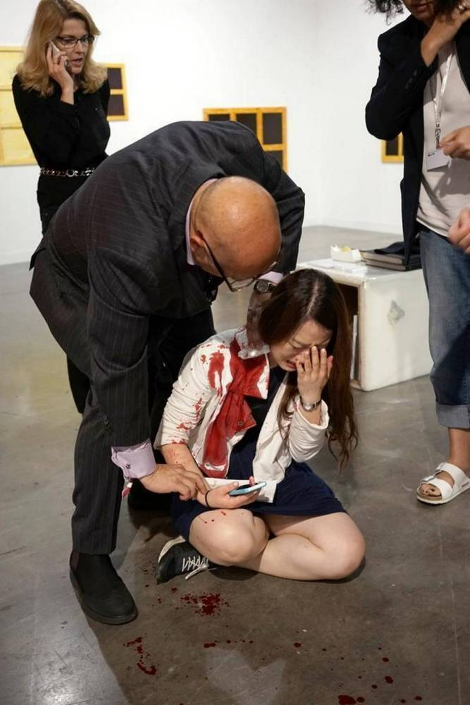 A man believed to be a physician takes the pulse of a woman who was stabbed at Art Basel, inside the Miami Beach Convention Center on Friday night, Dec. 4, 2015. RUDY PEREZ FOR THE MIAMI HERALD