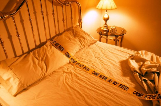 B1YYJY Unmade bed with police crime scene tape