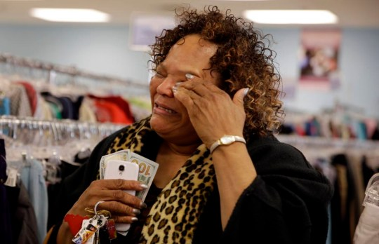 Debra Harris cries after receiving $200 from an anonymous man know known as Secret Santa, Wednesday, Dec. 9, 2015, in Jennings, Mo. Secret Santa is an anonymous Kansas City-area man who hands out $100 bills to the needy during the holiday season and is following in the footsteps his predecessor, Larry Stewart, who, over a quarter-century, gave away over $1 million before dying from cancer in 2007. (AP Photo/Jeff Roberson)