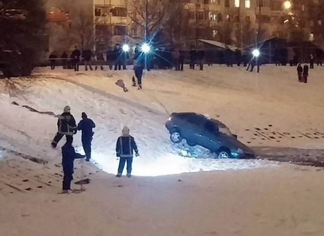 """Pic shows: the rescuers pull out the car from water. This is the moment a Lada plunged through thin ice after its owner bet friends he could manage to drive over a frozen lake. The bizarre bet took place next to the lake in the city of Zelenograd in western Russia's Moscow Oblast region. Footage of the incident shows a car driving in the dark on a pond covered with ice. After slowly approaching the edge of the frozen body of water where the ice is thinnest, the driver edges out onto the surface before speeding up and turning round in a sharp circle driving back to the shore. A man making a video in the background can be heard encouraging the driver to go ever further out, but suddenly the ice cracks and the car starts to sink. When the ice cracks, he starts urging his friend to head to the shore but too late. He says: """"The ice has cracked, get back, if it breaks youíll have to swim all the way here on your own, I wonít go in there. He then adds: """"This is how 200,000 roubles (1,868 GBP) sunk in a pond."""" Witnesses say that the men, who made a bet, were in the age span of around 18 to 22 years old and most likely had been drinking. Other footage later shows the man who escaped from the sinking car declaring: """"I just drowned my Lada. The ice turned out to be too thin."""" Members of the local emergency services eventually recovered the car from under the water. Now the owner is likely to get a hefty fine for pollution and wreaking havoc in a public place. (ends)"""