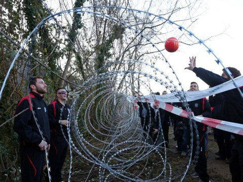 Locals and refugees play volleyball over razor wire fence at Slovenia border