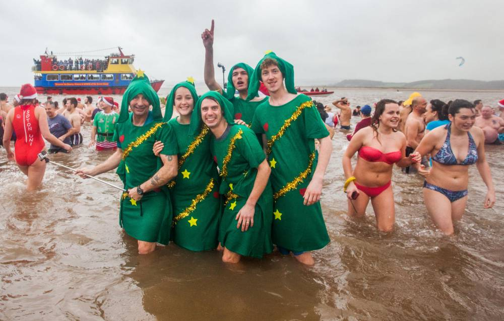 Hundreds of people gathered at the Exmouth seafront in Devon, to take part in the Christmas day swim. 25/12/2015 See SWNS story SWWET; Over a thousand revellers braved the winter weather to take part in a massive Christmas event - as they donned their swimming gear and dived into the icy water. Scores of people arrived on a British beach this morning to take part in the annual Christmas swim, which sees people flocking from all over the country to take part. Over 80 outdoor swims are held over the festive period, with most taking part on Christmas or Boxing Day. But the annual Christmas Swim in Exmouth, Devon has become an iconic event, and residents from all over the country head to the small town in fancy dress to take part in the swim.