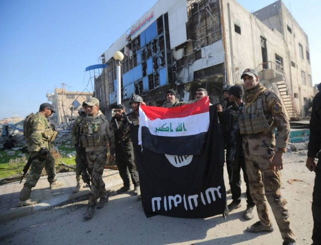 Members of the Iraqi security forces hold an Iraqi flag with an Islamic State flag which they had pulled down at a government complex in the city of Ramadi, December 28, 2015. REUTERS/Stringer EDITORIAL USE ONLY. NO RESALES. NO ARCHIVE TPX IMAGES OF THE DAY