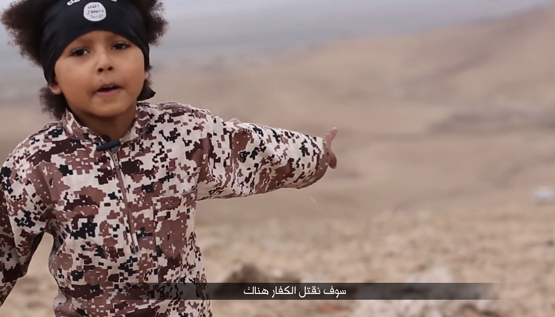 A young boy in the video apparently points to where the men should be killed
