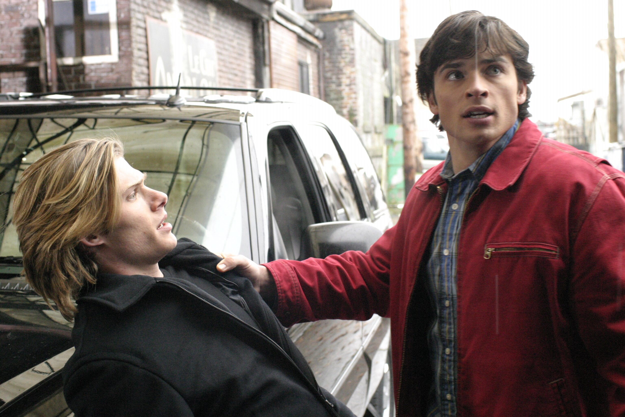 Television Programme. Smallville. E4. Picture shows Tom Welling with Chris Carmack in front of a car.