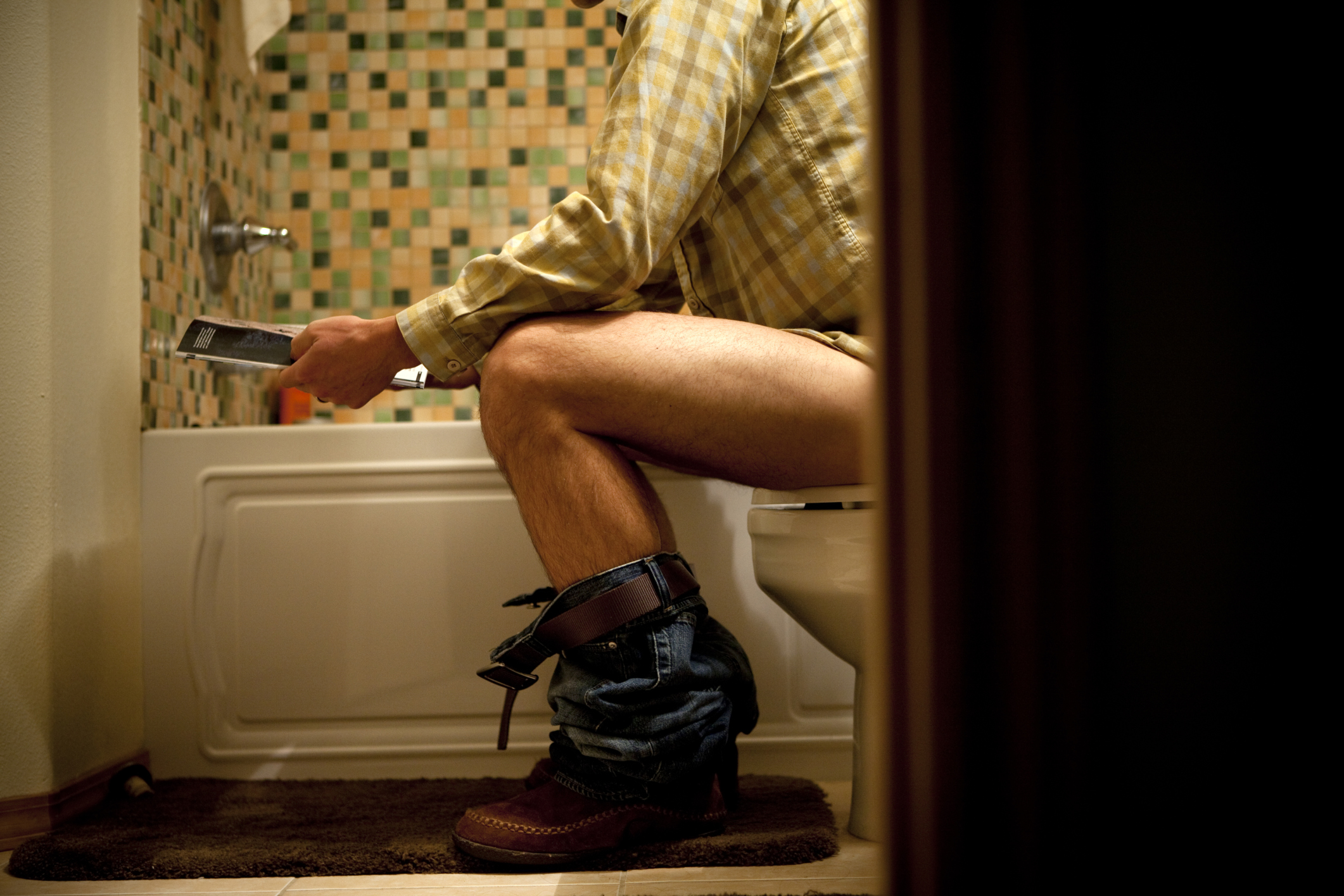 Male reading magazine on toilet.