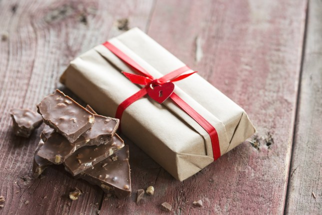 Pieces of chocolate candy bar near Christmas gift