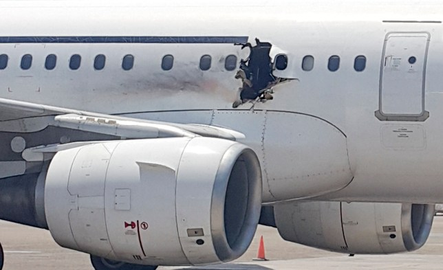 In this Tuesday, Feb. 2, 2016 photo, a hole is photographed in a plane operated by Daallo Airlines as it sits on the runway of the airport in Mogadishu, Somalia. A gaping hole in the commercial airliner forced it to make an emergency landing at Mogadishu's international airport late Tuesday, officials and witnesses said. (AP Photo)