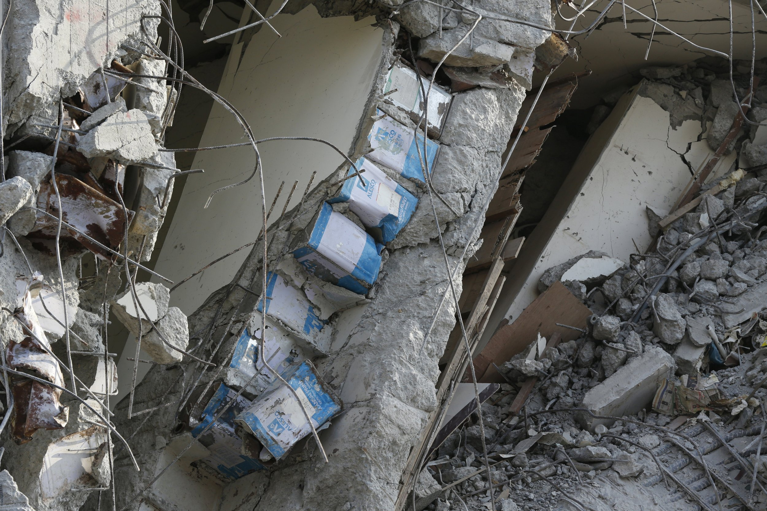 In this Sunday, Feb. 7, 2016, photo, tin cans are exposed in the cement structure of the collapsed building complex in Tainan, Taiwan. More than 100 people are believed to be still buried in the collapsed building from a disaster that struck during the most important family holiday in the Chinese calendar ó the Lunar New Year holiday. (AP Photo/Wally Santana