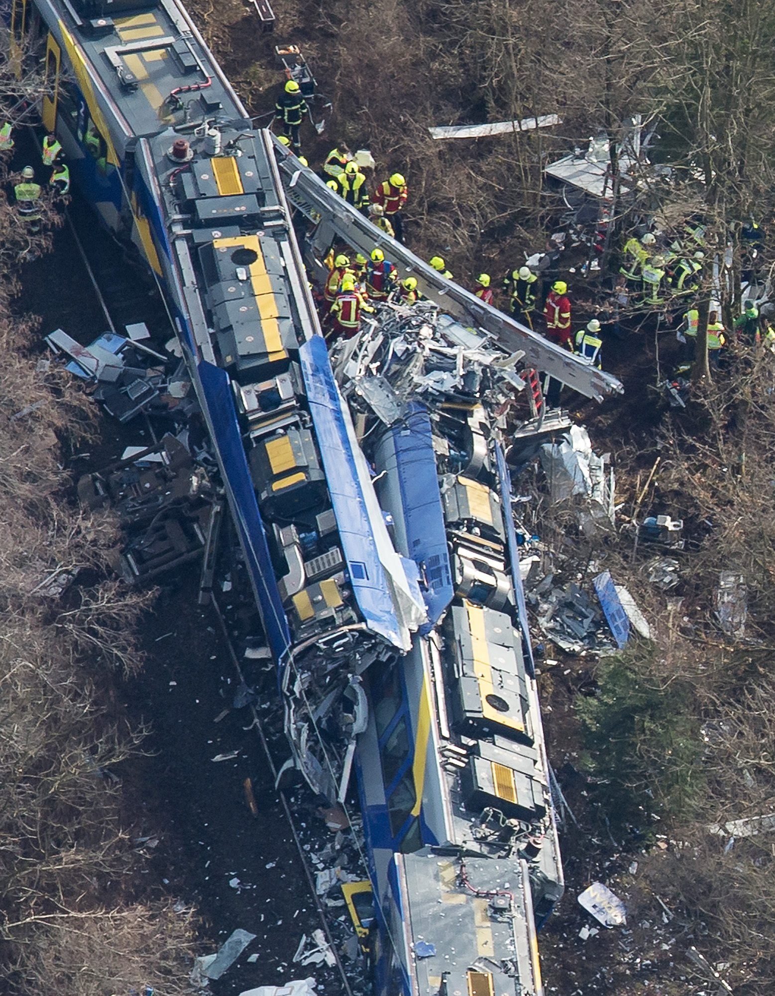 epa05151013 An aerial view of rescue forces working at the site of a train accident near Bad Aibling,¿Germany, 09 February 2016. At least eight people are dead and another 90 injured after two commuter trains collided head on near the southern German town of Bad Aibling, police said. EPA/PETER KNEFFEL