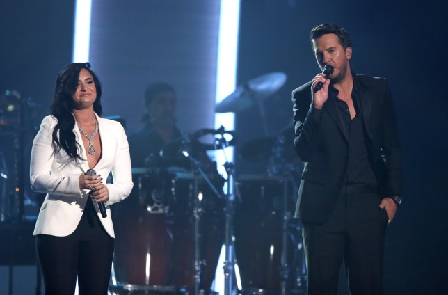 """Demi Lovato, left, and Luke Bryan perform """"Penny Lover"""" for a tribute to MusiCares Person of the Year honoree Lionel Richie at the 58th annual Grammy Awards on Monday, Feb. 15, 2016, in Los Angeles. (Photo by Matt Sayles/Invision/AP)"""