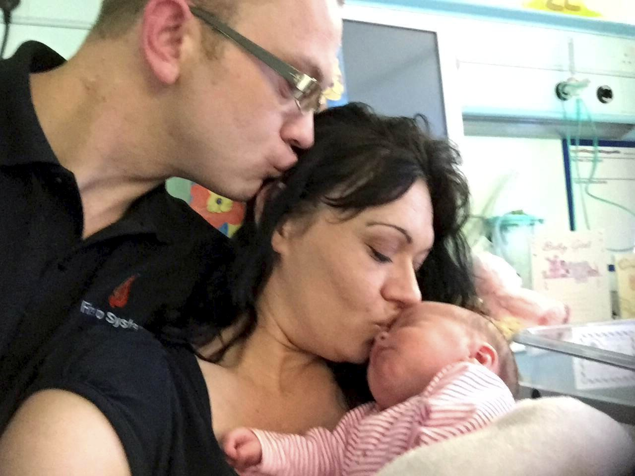 """Collect photo of Donna Cross who was attacked on her doorstep pictured with partner Jon Stone and their daughter Jordannah-Skye. See SWNS story SWSTAB; A new mum was inches from death after she told noisy yobs they were waking her baby - and one stabbed her in the chest. Donna Cross had """"reached the end of her tether"""" with the gang after they woke up eight-week-old daughter Jordannah-Skye. The new mum was stabbed in the chest - narrowly missing her heart - by one of the thugs after telling them to """"shut up"""". Donna was rushed to King's Cross Hospital for emergency surgery after losing two-and-a-half pints of blood. She also suffered damage to her breast-bone."""
