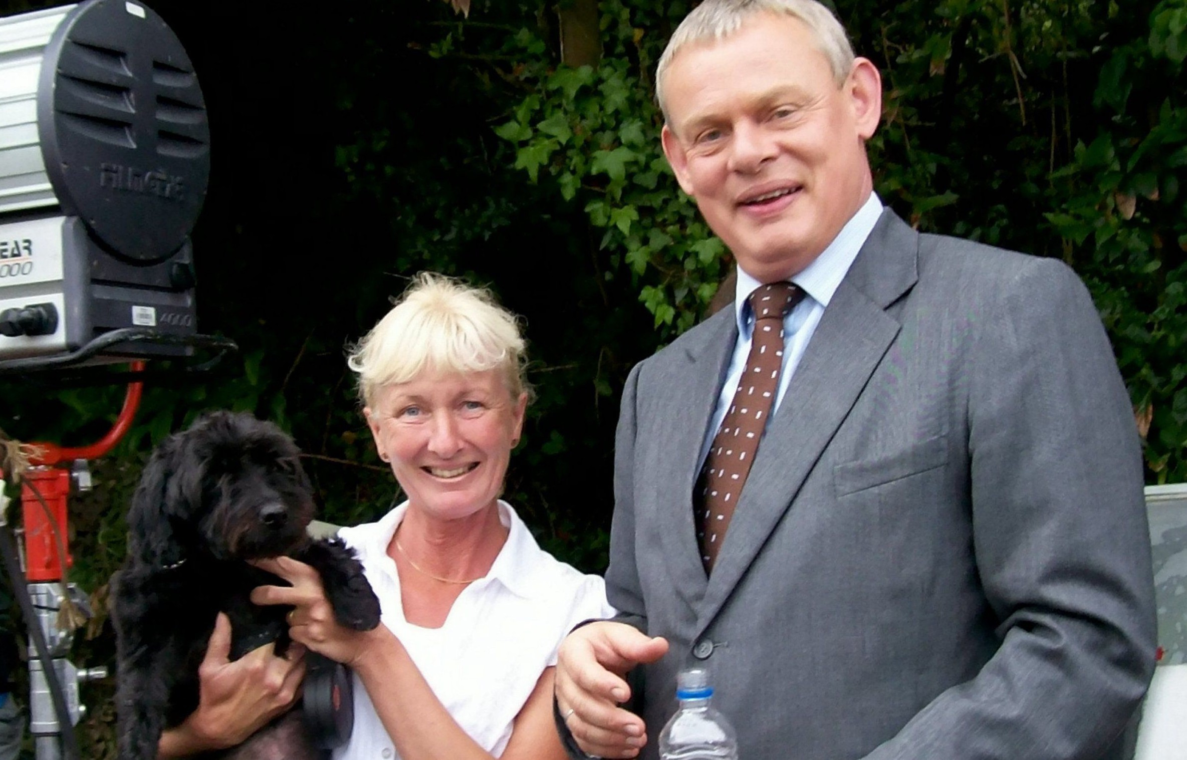 """Jane Wilson, Pippin and Martin Clunes on set. Actor Martin Clunes has offered a £2000 reward to try to find a stolen dog from Leicestershire. See NTI story NTIDOG. The 54-year-old star of TV show Doc Martin has made the generous gesture after Pippin was stolen in smash-and-grab raid at a house in Wigston, Leicester last Tuesday morning, March 15, 2016. Gareth Wilson, the owner of Pippin - a 15-year-old black yoodle, contacted the actor's agent in a desperate bid to find his beloved pet. Gareth said Pippin, a cross between a Yorkshire terrier and a poodle, is seriously ill and needs daily medicine to keep him alive. He said: """"My mother Jane took Pippin on holiday to Cornwall a few years ago. She is big fan of Martin Clunes so she went to the set in Port Isaac where they were filming the show. She got to meet Martin and he got to meet Pippin. She said he was lovely and was genuinely interested in Pippin.î"""