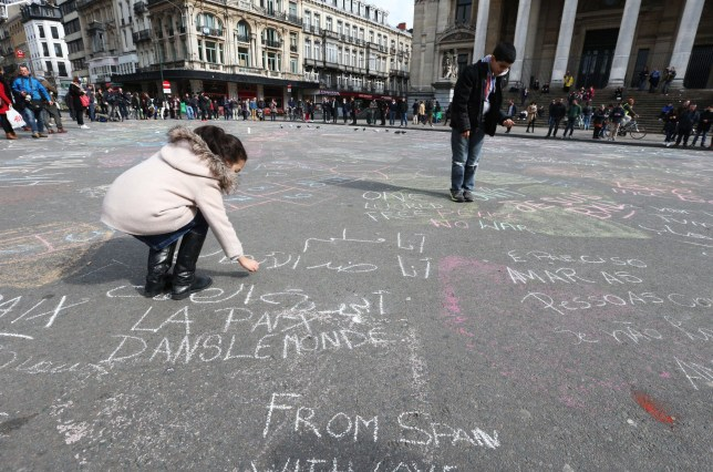 Mandatory Credit: Photo by Nicolas Maeterlinck/Belga vi/REX/Shutterstock (5617879t) People write down messages at the Bourse - Beurs building in the city center of Brussels, after today's terrorist attacks Explosions in Brussels, Belgium - 22 Mar 2016 Two explosions in the departure hall of Brussels Airport this morning took the lives of 14 people, 81 got injured. Another explosion happened in the Maelbeek - Maalbeek subway station, 15 deaths and around 70 injured people were confirmed by Brussels' public transport company STIB-MIVB. Government sources speak of a terrorist attack. The terrorist threat level has been heightened to four across the country