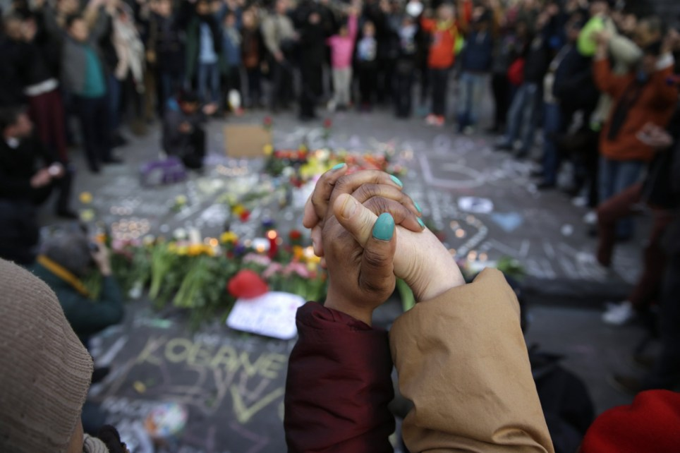 People stand hand in hand in tribute to victims at a makeshift memorial in front of the stock exchange at the Place de la Bourse (Beursplein) in Brussels on March 22, 2016, following triple bomb attacks in the Belgian capital that killed about 35 people and left more than 200 people wounded. A series of explosions claimed by the Islamic State group ripped through Brussels airport and a metro train on March 22, killing around 35 people in the latest attacks to bring bloody carnage to the heart of Europe. AFP PHOTO / KENZO TRIBOUILLARDKENZO TRIBOUILLARD/AFP/Getty Images