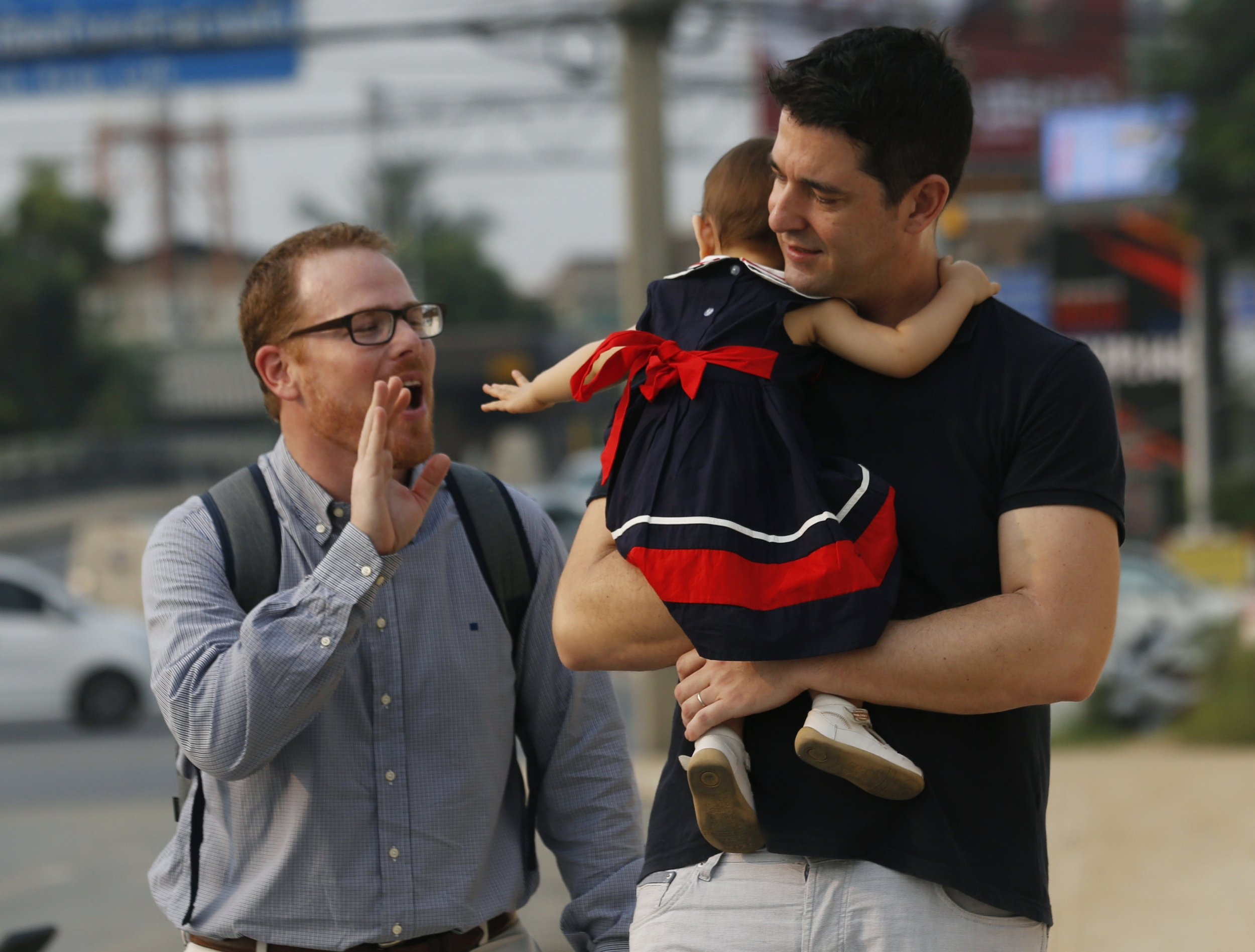 American Gordon Lake, left, and Manuel Santos, right, walk with their baby Carmen, center, at the Central Juvenile and Family Court in Bangkok, Thailand, Wednesday, March 23, 2016. The couple has opened a high-profile custody battle in Thailand for a baby girl born to a surrogate mother, who decided she wanted to keep the child when she found out they were gay. (AP Photo/Sakchai Lalit)