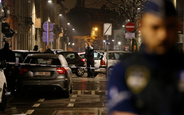 Police guard a check point and man positions during a police raid in the suburb of Schaerbeek in Brussels, early Friday, March, 25, 2016. Belgium's prime minister refused to accept the resignations of his justice and interior ministers Thursday despite increasing evidence of intelligence and law enforcement failures to prevent this week's suicide bombings by Islamic militants.(AP Photo/Alastair Grant)