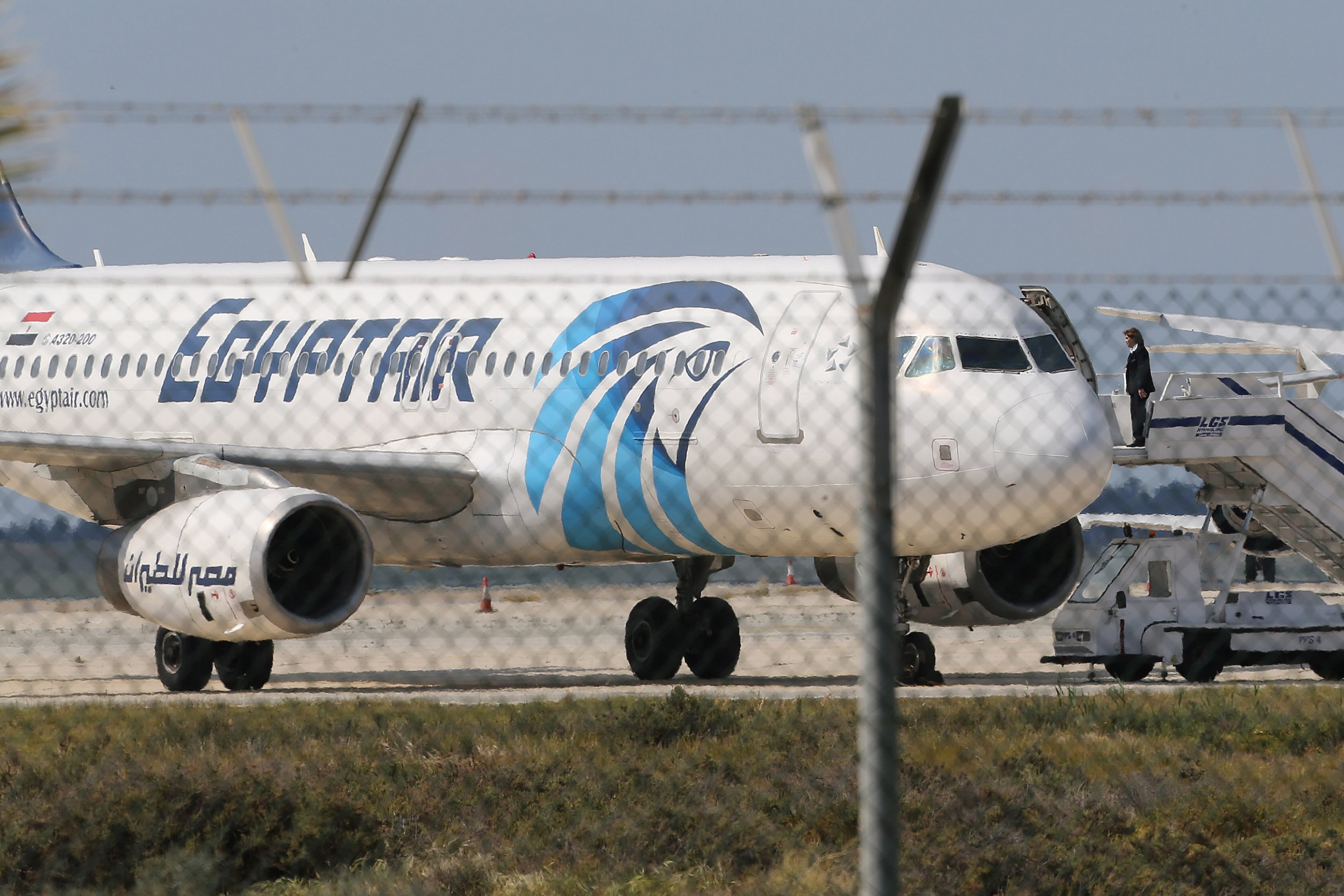 A crew member of the hijacked aircraft of EgyptAir is seen on the passenger steps after landing at Larnaca airport Tuesday, March 29, 2016. The EgyptAir plane was hijacked on Tuesday while flying from the Egyptian Mediterranean coastal city of Alexandria to the capital, Cairo, and later landed in Cyprus where some of the women and children were allowed to get off the aircraft, according to Egyptian and Cypriot officials. (AP Photo/Petros Karadjias)