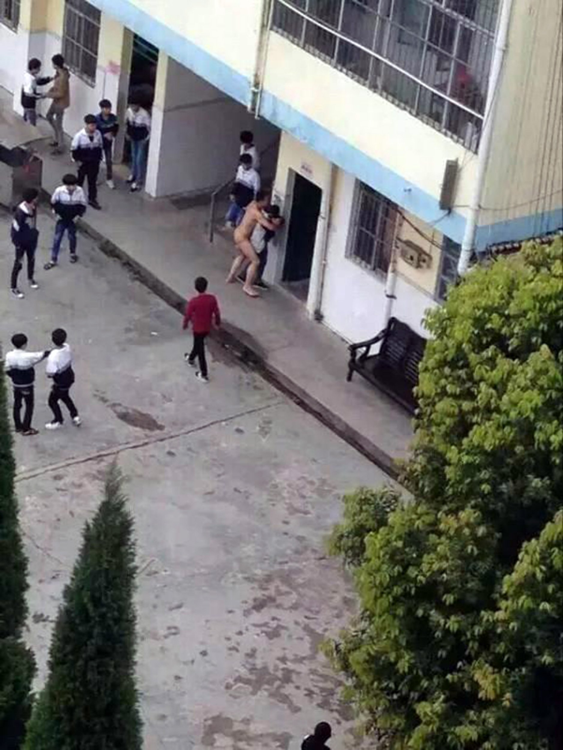 """Pic shows: Hou attempts to ërapeí the victim. Shocking photos have emerged from a Chinese high school where one of the faculty members stripped naked and attempted to rape a female pupil. The now viral photos show the employee, reportedly mentally ill, in the nude, bear-hugging the victim from behind while shocked pupils watch on in horror. Reports from Lingshan County, in South Chinaís Guangxi Zhuang Autonomous Region, said that the 30-year-old suspect, surnamed Hou, worked as a caretaker for Taiping Middle Schoolís laboratories. Hou is said to have stormed out of a school building unclothed, after which he picked out a female pupil at random and began ëharassingí her. As at least six other schoolboys stood watching in shock, Hou pushed the victim against the exterior wall of a classroom while she screamed for help. Nearby teachers soon intervened and helped subdue Hou, who had been employed by the high school for a number of years. Local authorities then detained Hou, who reportedly has a history of suffering mental illness. The specifics of Houís illness were not mentioned in reports. A police spokesman said: """"The suspect appears to have been suffering from mental disorders since 2011, but doctors said he would have been fine if the illness had not returned in two years."""" The victim reportedly did not suffer any physical pain, but will be referred to a psychiatrist for possible emotional and psychological trauma. It is as of yet unclear whether Hou will be immediately relieved of his position at the school following the incident. (ends)"""