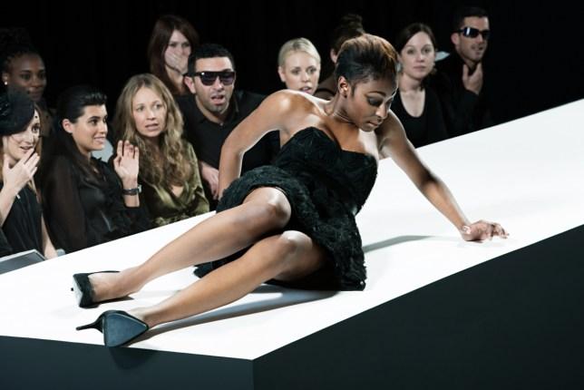 Model sitting on catwalk having fallen down at fashion show