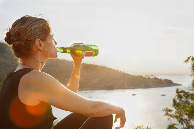 woman enjoying a beer in the sunset up a bay