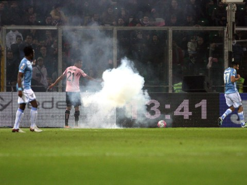 Lazio's Serie A match with Palermo halted twice after fans throw flares onto the pitch