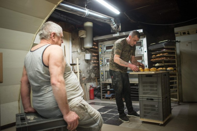 TO GO WITH AFP STORY BY ANGELA SCHNAEBELE (FILES) This file photo taken on March 23, 2016 shows Michel Flamant (L) and Jerome (R) working in their bakery on March 23, 2016, in Dole, eastern France. Michel Flamant, the owner of the bakery decided to teach baking and pastry to Jerome and to sell him his bakery for one symbolic euro, after Jerome saved his life. / AFP PHOTO / SEBASTIEN BOZONSEBASTIEN BOZON/AFP/Getty Images