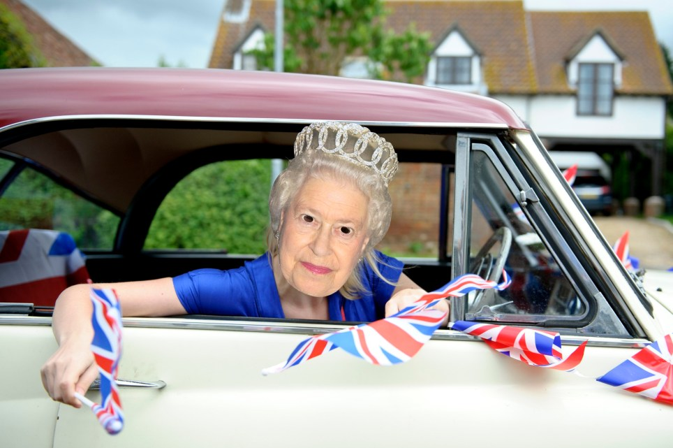 TEMPSFORD, UNITED KINGDOM - JUNE 04: A reveller wears a Queen Elizabeth II mask as she leans out of a car window, during a countryside Diamond Jubilee street party on June 4, 2012 in Church St, Tempsford, United Kingdom. For only the second time in its history the UK celebrates the Diamond Jubilee of a monarch. Her Majesty Queen Elizabeth II celebrates the 60th anniversary of her ascension to the throne. (Photo by Ben Pruchnie/FilmMagic)