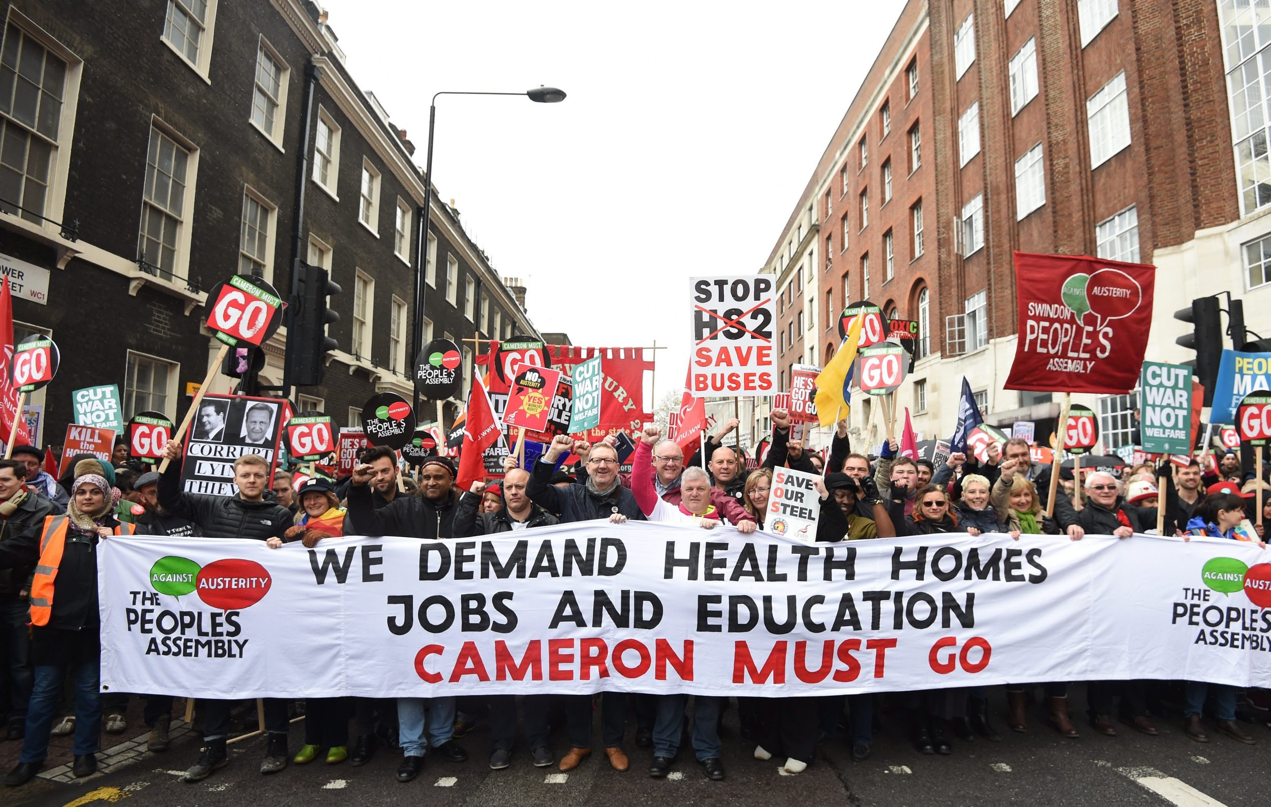 epa05262097 Protestors hold placards as they march during an Anti-Austerity National demonstration in London, Britain, 16 April 2016. The march under the slogan,'Health, Homes, Jobs and Education, Cameron Must Go, Tories Out!' was organized by the People's Assembly against Austerity. EPA/FACUNDO ARRIZABALAGA
