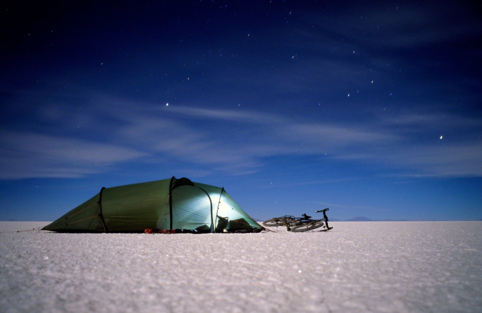 XX best stargazing spots around the world A6T8T3 Tent and bicycle on salt flat of Salar de Uyuni in Bolivia at 3600 mteres altitude at midnight with star trails in deep blue nig David Myers Photography / Alamy Stock Photo