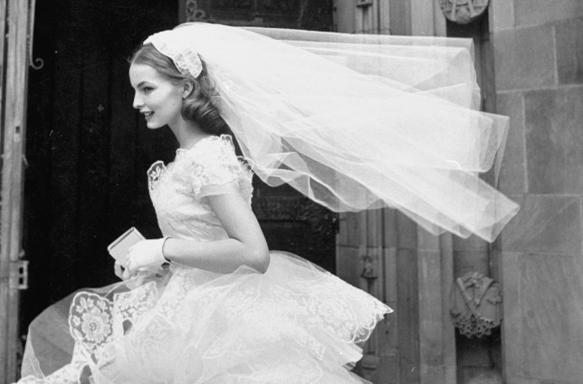 Martha Boss, the country's top bridal model is wearing a nylon tulle lace gown and veil.