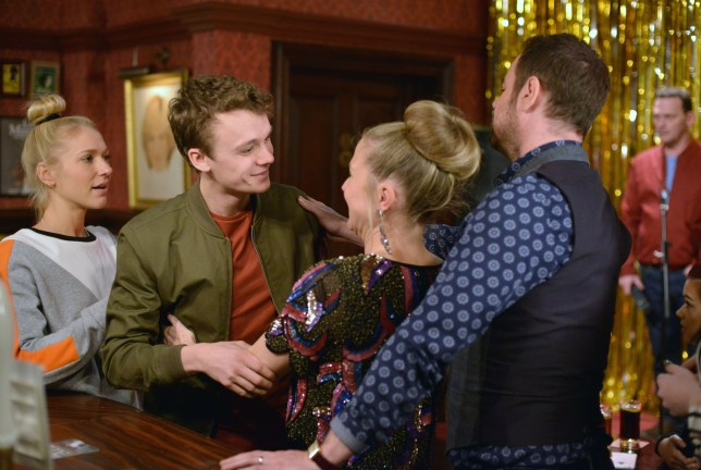 WARNING: Embargoed for publication until 00:00:01 on 05/04/2016 - Programme Name: EastEnders - TX: 12/04/2016 - Episode: 5262 (No. n/a) - Picture Shows: *STRICTLY NOT FOR PUBLICATION UNTIL 00:01HRS, TUESDAY 5TH APRIL, 2016* Linda hugs Johnny. Nancy Carter (MADDY HILL), Johnny Carter (TED REILLY), Linda Carter (KELLIE BRIGHT), Mick Carter (DANNY DYER) - (C) BBC - Photographer: Kieron McCarron