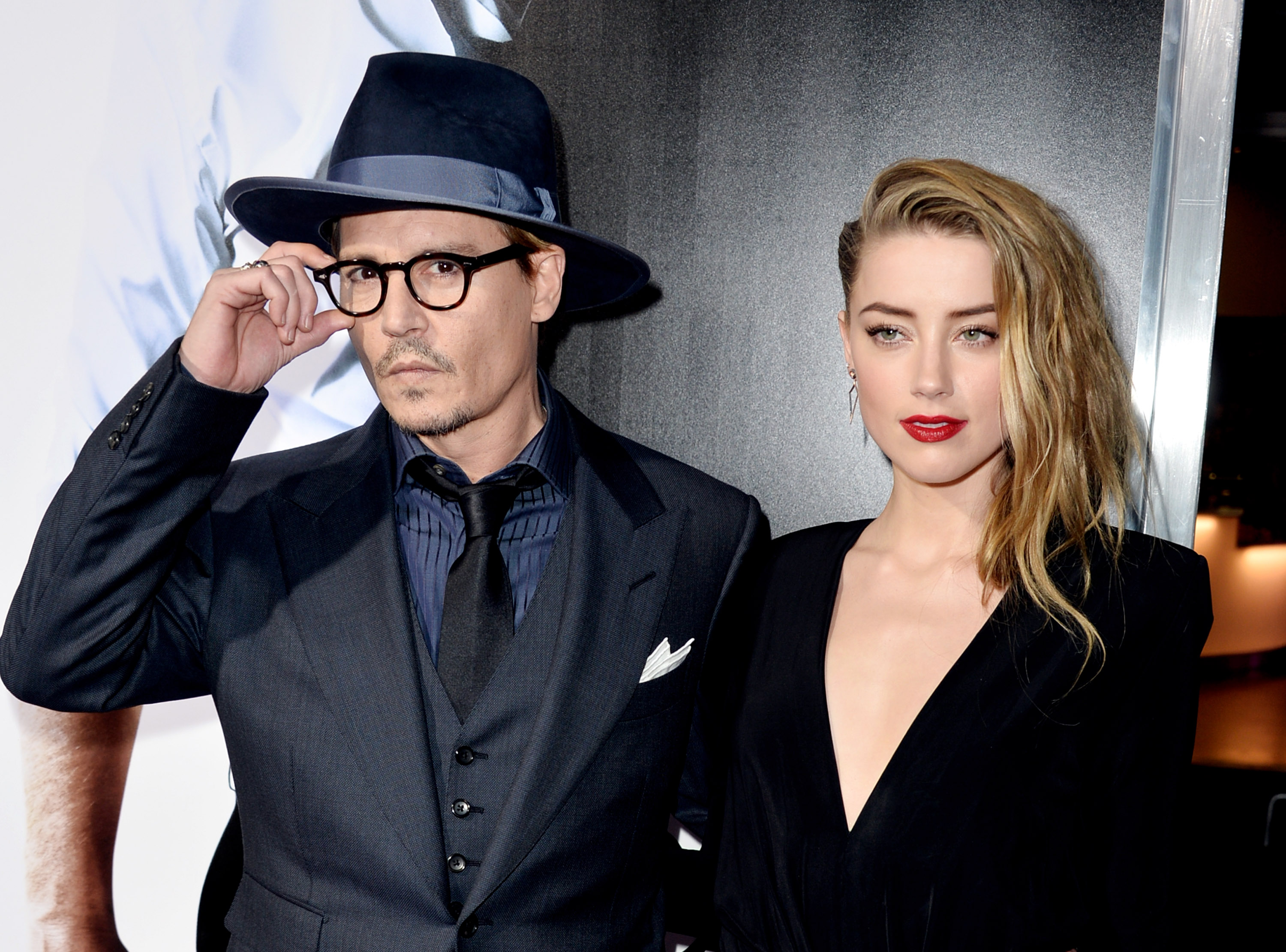 """LOS ANGELES, CA - FEBRUARY 12: Actor Johnny Depp (L) and his fiancee actress Amber Heard arrive at the premiere of Relativity Media's """"3 Days To Kill"""" at the Arclight Theatre on February 12, 2014 in Los Angeles, California. (Photo by Kevin Winter/Getty Images)"""