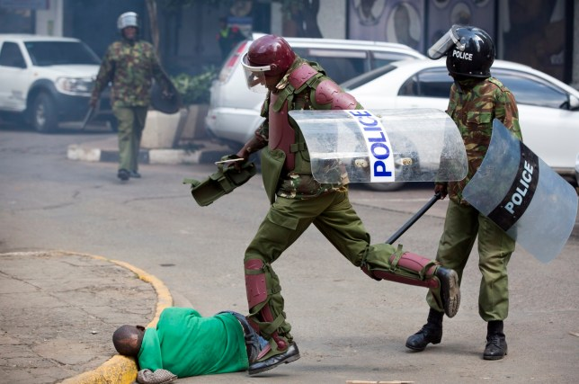 A Kenyan riot policeman repeatedly kicks a protester as he lies in the street after tripping over while trying to flee from them, during a protest in downtown Nairobi, Kenya, Monday, May 16, 2016. Kenyan police have tear-gassed and beaten opposition supporters during a protest demanding the disbandment of the electoral authority over alleged bias and corruption. (AP Photo/Ben Curtis)