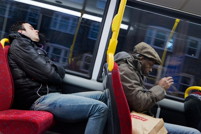 FB7HGH Two men listening to music on their phones on London bus