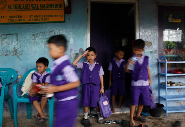 A child gestures inIndonesia will now castrate child sex offenders Credit: Reutersfront of a classroom while getting ready to go home after attending the first day of school, after the Christmas and New Year holidays, at an Islamic kindergarten at the Tanah Abang slum district in Jakarta January 7, 2013. Indonesia has more than one million children, mainly from poor families, who are not in school as of 2012, said Arist Merdeka Sirait, chief of the National Commission for Child Protection (Komnas PA), to a local newspaper in December 2012. REUTERS/Beawiharta (INDONESIA - Tags: EDUCATION RELIGION SOCIETY POVERTY) - RTR3C69I