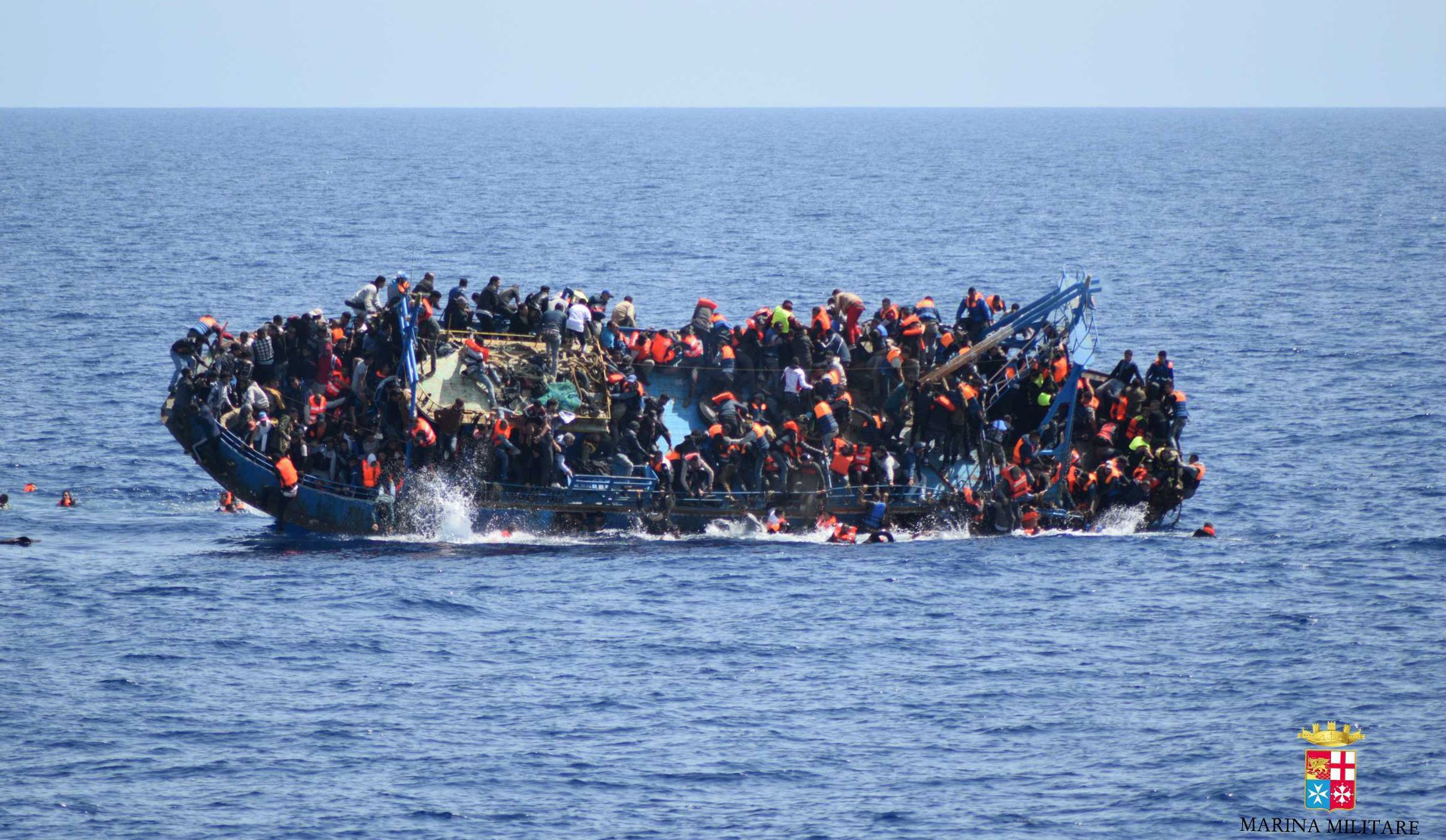 More than 880 migrants died in the Med last week. FILE - In this May 25, 2016 file photo made available by the Italian Navy, people try to jump in the water right before their boat overturns off the Libyan coast. Over 700 migrants are feared dead in three Mediterranean Sea shipwrecks south of Italy in the last few days as they tried desperately to reach Europe in unseaworthy smuggling boats, the U.N. refugee agency said Sunday, May 29, 2016. (Italian navy via AP Photo, file)